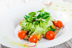 Ny sallad med det fega bröstet, behandla som ett barn spenat, grönsallat, körsbärsröda tomater och ost på träbakgrund Fotografering för Bildbyråer