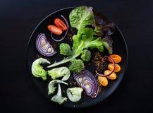 Ny sallad med grönsaker på en svart platta Royaltyfri Bild