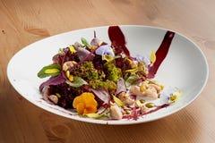 Ny sallad med höna, grönsallat och ätliga pansies på den vita plattan Arkivfoto