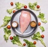 Ny sallad med körsbärsröda tomater, kryddor och örter, med det rå fega bröstet i en pannatappning, sportmatställeträlantlig backg Arkivfoto