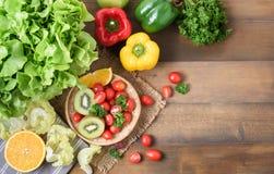 Ny salladgrönsaker och frukt på wood bakgrund arkivbild