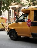 NY School Bus. Small school bus stops on the streets of a major city, surrounded by trash containers and graffitti Stock Photo