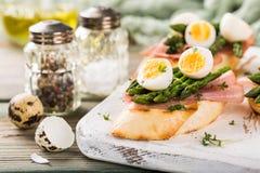 Ny sendwich med skinka-, sparris- och vaktelägg Royaltyfri Foto