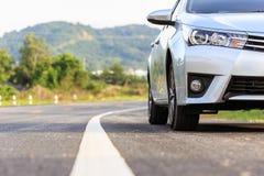 Ny silverbilparkering på asfaltvägen Arkivfoto