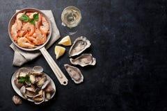 Ny skaldjur och vitt vin Kammusslor, ostron och räkor royaltyfria foton