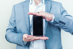 Ny skinande telefon i manliga händer Arkivbild