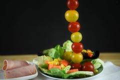 Ny skinkasallad på en platta med tomaterna i en högväxt vertikal linje för en idérik bild arkivfoto