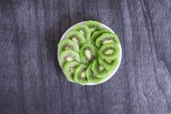 Ny skivad kiwi på plattan Gröna kiwiskivor på mörk träbakgrund Arkivbild