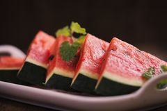 Ny skivad vattenmelon i den vita maträtten på trätabellen Royaltyfri Bild