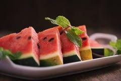 Ny skivad vattenmelon i den vita maträtten på trätabellen Arkivfoto