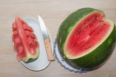 Ny skivad vattenmelon i den vita plattan vattenmelon som skivas på en platta på en träbakgrund Arkivbild