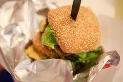 Ny smaklig hamburgare som isoleras på tabellen Arkivfoton