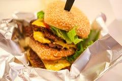 Ny smaklig hamburgare som isoleras på tabellen Arkivbilder