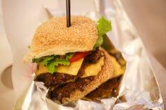 Ny smaklig hamburgare som isoleras på tabellen Royaltyfria Bilder
