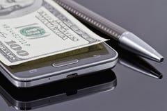Ny smartphone, kulspetspenna och hundra dollar Royaltyfria Foton