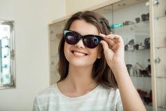 Ny solglasögon för flickasökanden som betonar hennes stil Inomhus skott av den gulliga kvinnliga caucasian flickan i lager som nå Arkivfoto