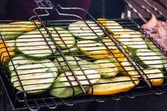 Ny sund grön zucchinizucchinigurka som förbereder sig på ett grillfestgaller över kol grillad skivazucchini Vegetarian, arkivfoto