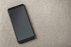 Ny svart modern mobiltelefon som isoleras på ljus bakgrund för torkdukekopieringsutrymme Modern teknologi, kommunikation och grej royaltyfri bild