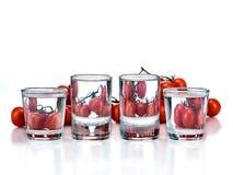 Ny tomat i ett exponeringsglas av vatten som isoleras på vit bakgrund arkivbild