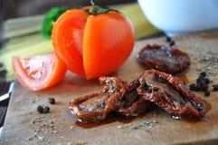 Ny tomat och torkad tomat med kryddor Fotografering för Bildbyråer