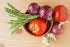 Ny tomater, haricot vert, lökar och vitlök på en trätabell Royaltyfri Fotografi