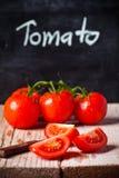 Ny tomater, kniv och svart tavla Arkivbilder