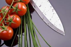 Ny tomater och kniv Arkivbild