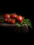 Ny tomater och persilja på åldrigt trä Svart bakgrund royaltyfri foto