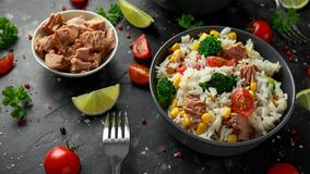 Ny tonfiskrissallad med majs, körsbärsröda tomater, broccoli, persilja och limefrukt i svart bunke royaltyfri fotografi