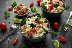Ny tonfiskrissallad med majs, körsbärsröda tomater, broccoli, persilja och limefrukt i svart bunke arkivfoton