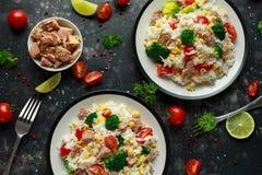 Ny tonfiskrissallad med majs, körsbärsröda tomater, broccoli, persilja och limefrukt i svart bunke arkivbilder