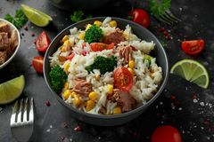 Ny tonfiskrissallad med majs, körsbärsröda tomater, broccoli, persilja och limefrukt i svart bunke arkivbild