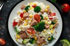 Ny tonfiskrissallad med majs, körsbärsröda tomater, broccoli, persilja och limefrukt i svart bunke royaltyfri bild