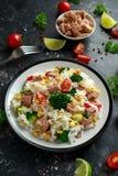 Ny tonfiskrissallad med majs, körsbärsröda tomater, broccoli, persilja och limefrukt i svart bunke royaltyfri foto