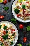 Ny tonfiskrissallad med majs, körsbärsröda tomater, broccoli, persilja och limefrukt i svart bunke royaltyfria bilder