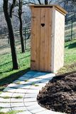 Ny trätoalett i trädgården - hjärta format hål på dörren royaltyfria foton