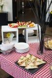 Ny triangulär form för klubbasmörgåsar med tomaten på en platta på tabellen i en expencive restaurang arkivfoton
