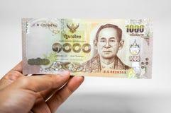 Ny tusen bahtsedel som visas i hand Arkivfoton