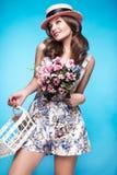 Ny ung flicka i sommarklänningen, leende, retro hattutvikningsbildstil med korgen av blommor Skönhetframsida, kropp Arkivbilder