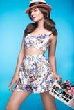 Ny ung flicka i sommarklänningen, leende, retro hattutvikningsbildstil med korgen av blommor Skönhetframsida, kropp Arkivbild