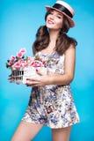 Ny ung flicka i sommarklänningen, leende, retro hattutvikningsbildstil med korgen av blommor Skönhetframsida, kropp Royaltyfria Bilder