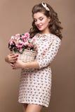 Ny ung flicka, ljus siden- klänning, leende, retro krullningsutvikningsbildstil med korgen av blommor Skönhetframsida, kropp Royaltyfri Foto