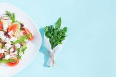 Ny vårsallad med gurkan, tomaten, ost och arugula som isoleras på en vit platta royaltyfri bild