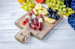 Ny vald äpplen och druvor och fruktpastill på mörk backg royaltyfria bilder