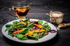 Ny vegetarisk sallad av arugula, mango och granatäpplet, vitaminmellanmål på en svart träbakgrund begrepp av lågt - kalori royaltyfri foto