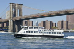 NY Waterway Ferry. A NY Waterway ferry boat passes the Brooklyn Bridge on the East River Stock Photography