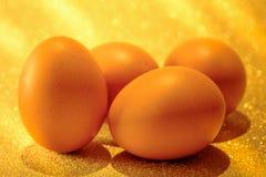 Nya ägg på guld- ljus av guld- bokehbakgrund Guld- H Royaltyfri Fotografi