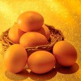 Nya ägg på guld- ljus av guld- bokehbakgrund Guld- H Royaltyfria Foton