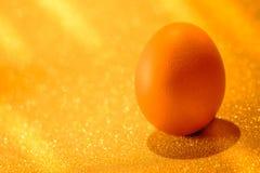Nya ägg på guld- ljus av guld- bokehbakgrund Guld- H Royaltyfri Foto