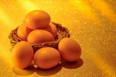 Nya ägg på guld- ljus av guld- bokehbakgrund Guld- H Arkivbild